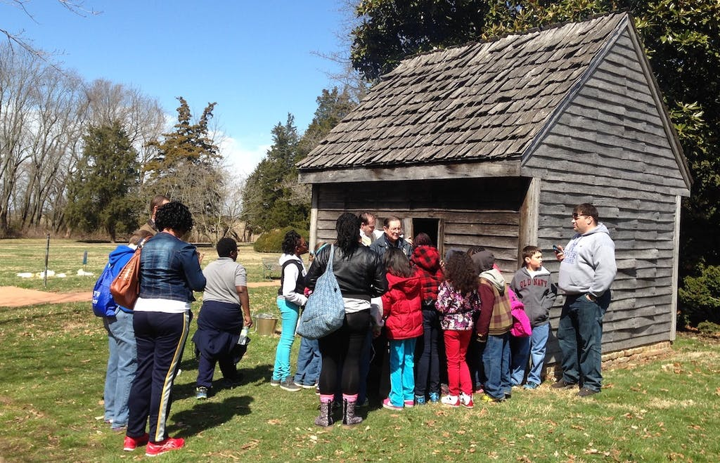 A replica log'd dwelling, the type of housing inhabited by enslaved people, tenants and indentured servants. The mansion is in the background. (Delaware Division of Historical and Cultural Affairs)