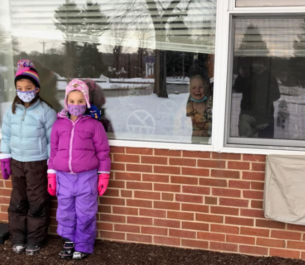 The smile on the resident in the window leaves no doubt they enjoyed watching the kids build snowmen.